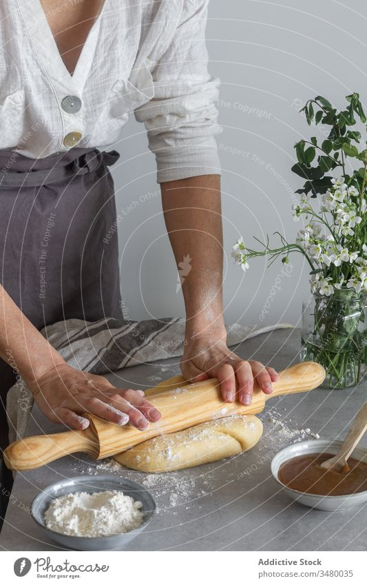Crop female rolling pastry dough woman cook rolling pin table flour apple puree flower bouquet apron tool utensil kitchen prepare food ingredient cuisine recipe