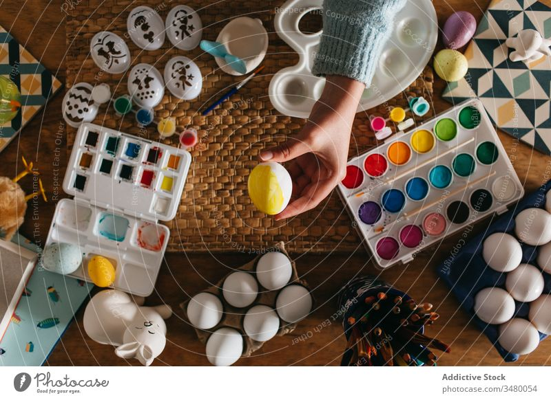 Crop person showing unfinished Easter egg easter paint table home holiday prepare creative art tradition celebrate design handmade christian festive composition