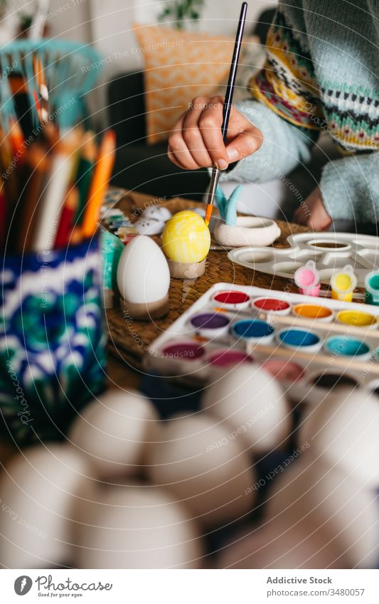 Crop person painting Easter eggs easter holiday tradition colorful brush creative art craft handmade hobby table design vibrant vivid bright decor festive