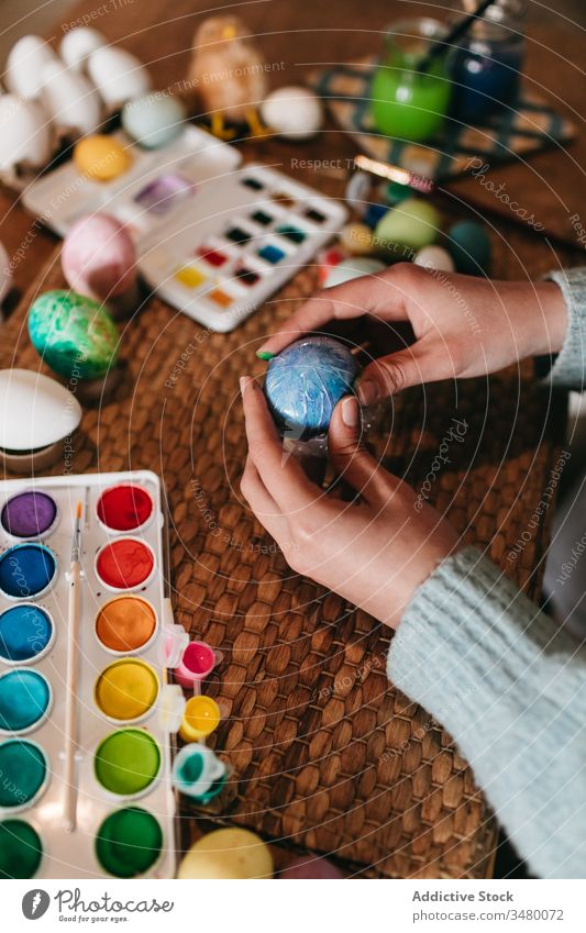 Crop person making ornament on Easter egg paint easter film wrap table home prepare holiday creative colorful art homemade design tradition hobby handmade craft
