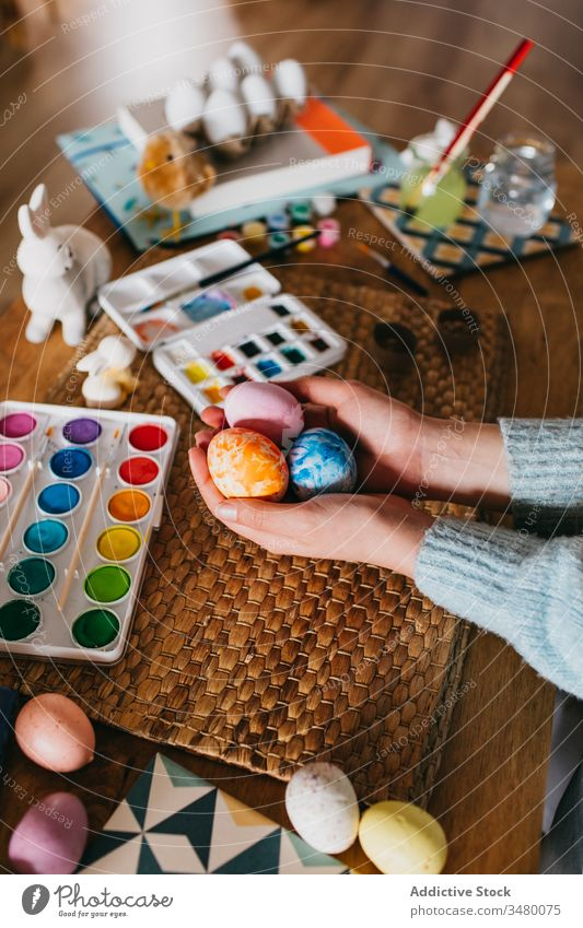 Crop person showing finished Easter egg easter paint table home holiday prepare creative art tradition celebrate design handmade christian festive composition