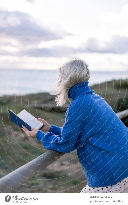 Young woman reading book near sea fence beach casual rest young blue enjoy poetry sweater nature relax female wooden style alone modern trendy blond recreation