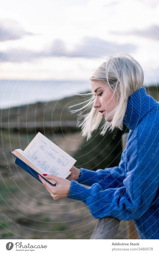 Young woman reading book near sea fence beach rest young blue enjoy poetry sweater nature relax female wooden style alone modern trendy blond calm seaside