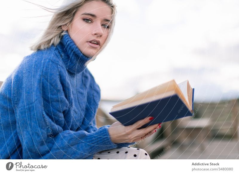 Young woman reading book on seashore terrace bench beach rest young blue sweater nature relax female wooden style vacation enjoy holiday modern trendy blond