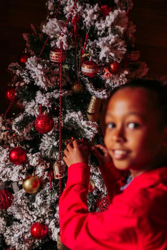 Happy little girl decorating Christmas tree kid christmas decorate tradition home rustic ethnic smile happy casual cheerful positive female enjoy festive black