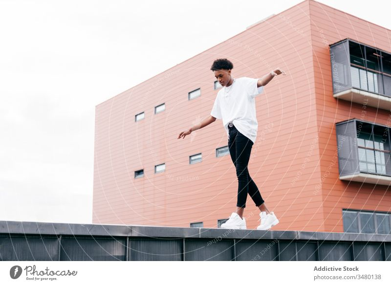 Fashionable ethnic man standing against modern building street style fashion trendy cool urban young city confident african american black contemporary outfit