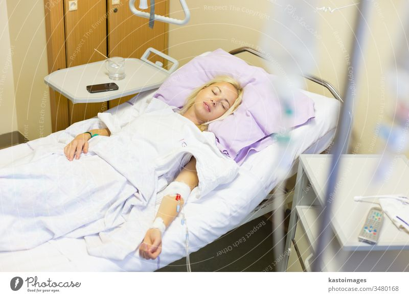 Bedridden female patient recovering after surgery in hospital care. bed sick woman healthcare medical medicine ill room recovery illness ward bedridden