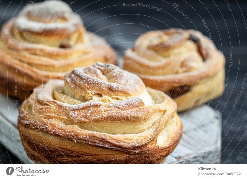 Bakery products with raisins and dried fruits are located on a dark wooden background. Sprinkled with icing sugar. Kraffins. Easter food. buns kraffins baking