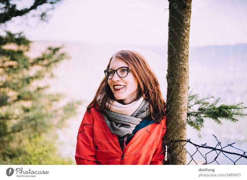 Young woman with a red jacket leans relaxed against a tree and smiles with the sun take a walk To go for a walk Adventure Healthy gap Hill Hiking Tourism