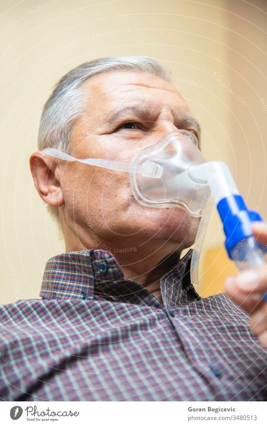 Senior man using medical equipment for inhalation with respiratory mask, nebulizer aerosol air allergy asthma asthmatic breath breathing bronchial bronchitis