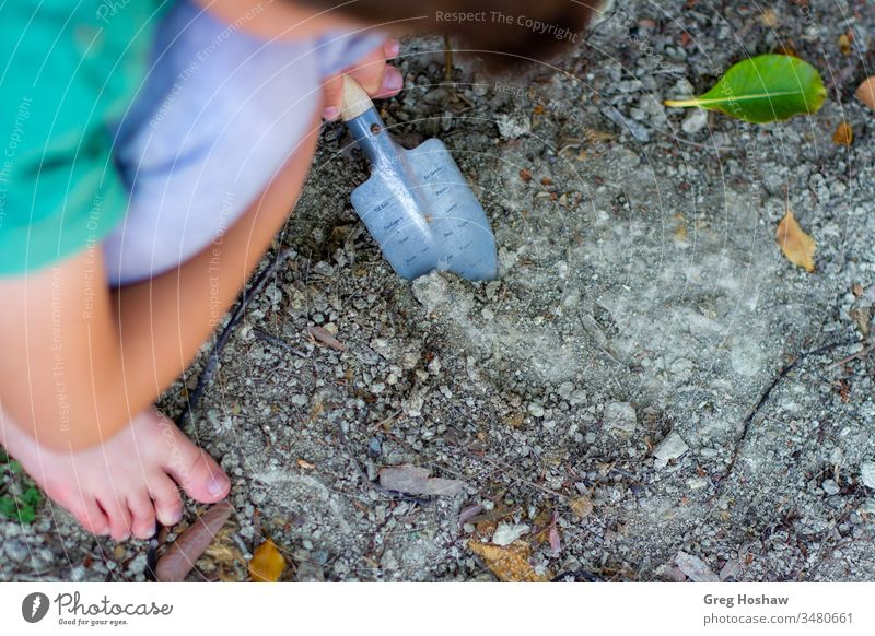 Barefoot child digging in dirt with shovel children kids boy son playing outside garden gardening exterior shot playing in dirt people joy backyard young