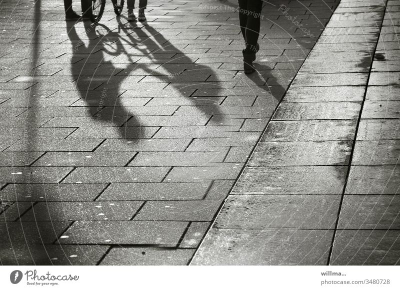 Public shading of persons in the city centre Shadow Shadow play people Bicycle Leisure and hobbies Footpath Boulevard Group maintain meetings Silhouette Street