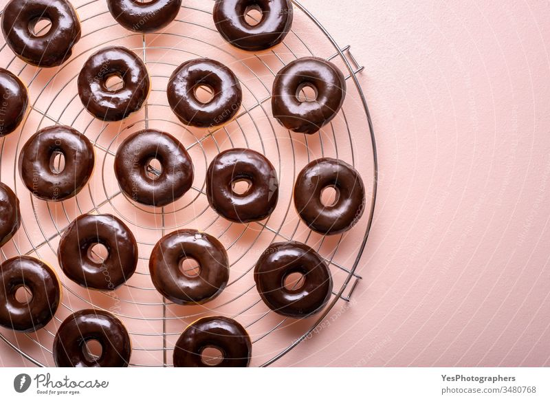 Hot donuts with melted chocolate on a cooling rack. Preparing choco doughnuts above view aligned background bakery carbs choco donuts chocolate glaze close-up