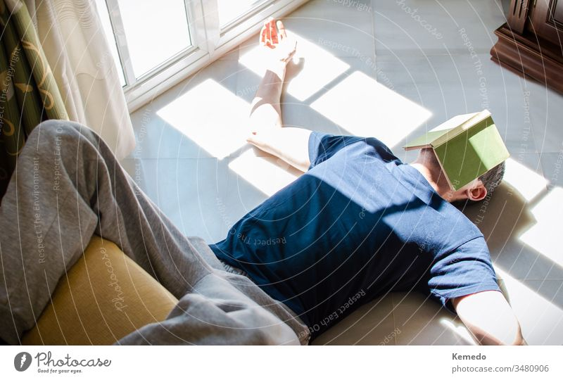 Young man resting on the floor whit a book on his face while enjoying the sun coming through the window. Concept of stay at home, freedom, boredom... leisure