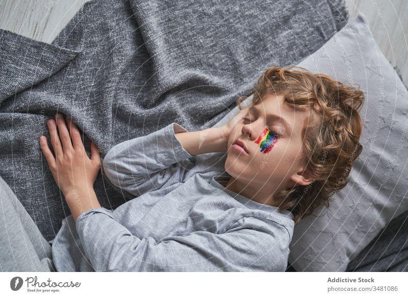 Boy with rainbow on face sleeping on floor boy home quarantine symbol lying down kid blanket pillow child nap snooze asleep eyes closed pandemic epidemic rest