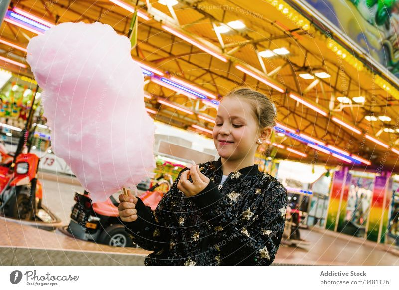 Girl eating cotton candy on funfair girl candyfloss smile lights city entertainment kid happy child urban sweet delighted treat lifestyle cheerful little sugar