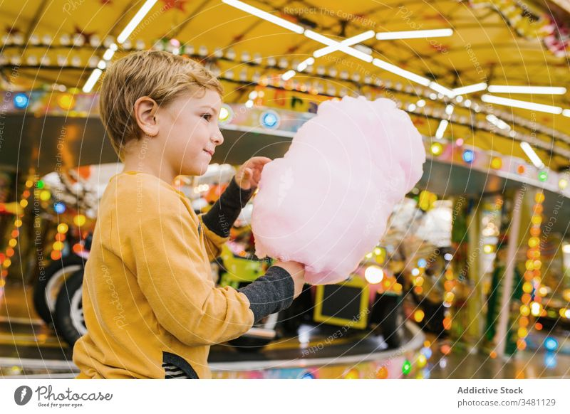Boy eating cotton candy on funfair boy candyfloss smile lights city entertainment kid happy child urban sweet delighted treat lifestyle cheerful little sugar