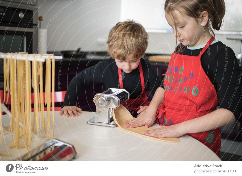 Kids preparing noodles at home kid pasta make machine together sibling kitchen homemade prepare cut sister brother children food apron cook culinary equipment