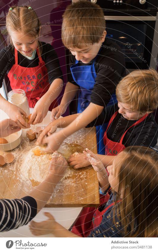 Children preparing dough together kid kitchen cook flour table prepare food children apron cute ingredient pasta help little cuisine meal home lifestyle counter