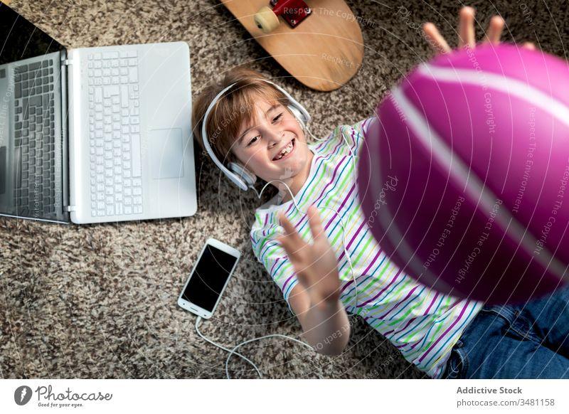 Happy boy having fun at home kid gadget music play ball toss lounge headphones smartphone throw up cheerful happy listen lying floor child device modern