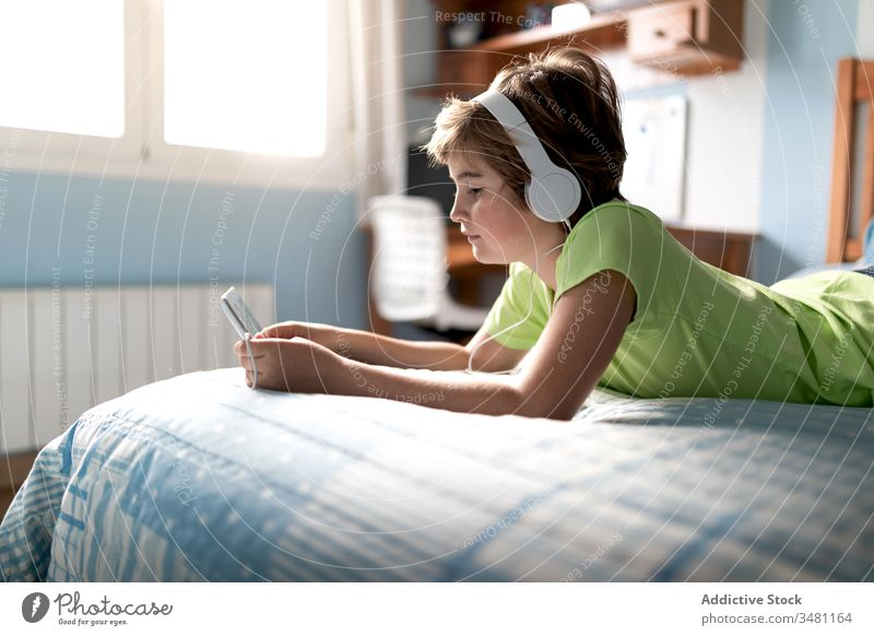 Cheerful kid watching movie on tablet in bedroom gadget home headphones cheerful boy using laugh child online listen internet happy lifestyle device modern