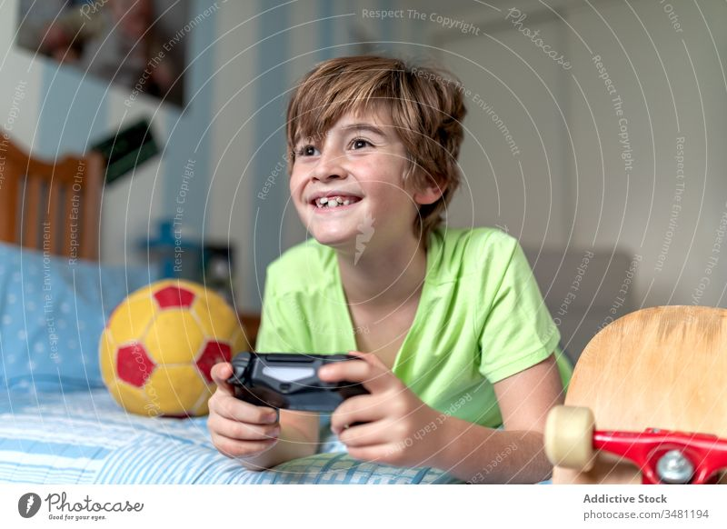 Happy boy playing video game in bedroom kid fun gamepad device excited gadget home lying cheerful using console child happy lifestyle modern connection digital