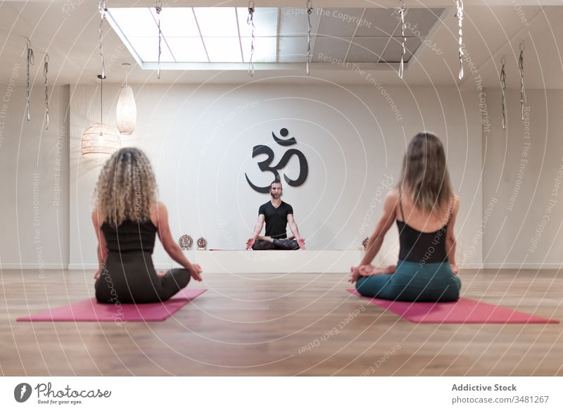 Group of people sitting on lotus pose on mats women man yoga room class body healthy mudra relaxation workout together wellness concentration recreation