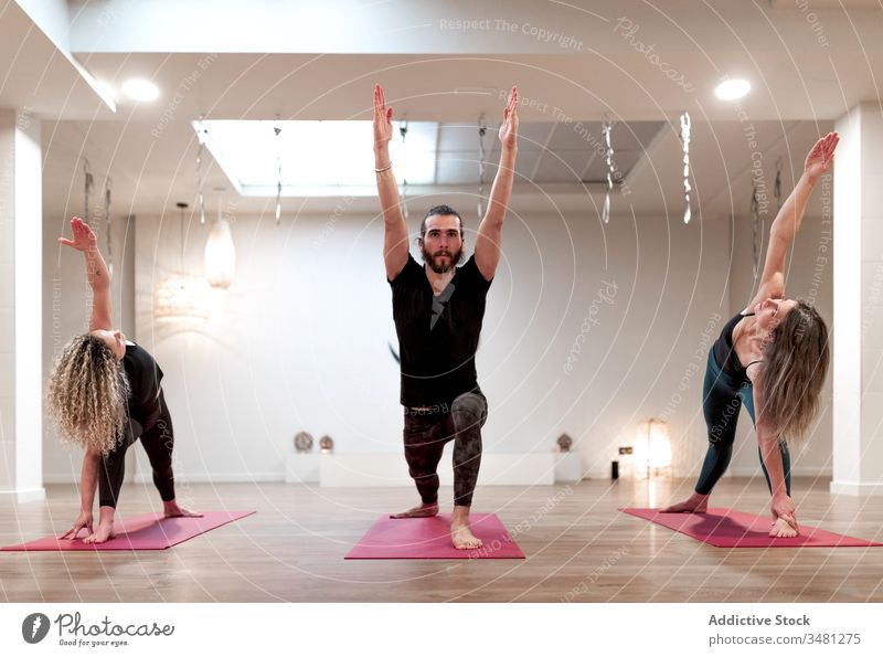 Group of people doing warrior pose and extended side angle pose on yoga women stretching man room raising hand class body healthy relaxation workout training