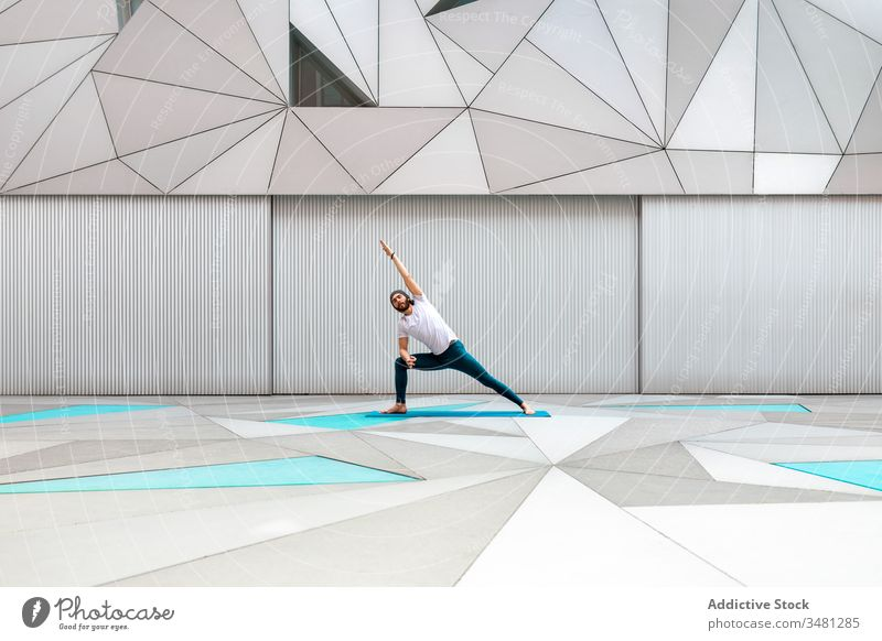 Man doing yoga exercise in geometric room man training geometry side angle pose modern stretch fitness shape male sportswear architecture contemporary wall