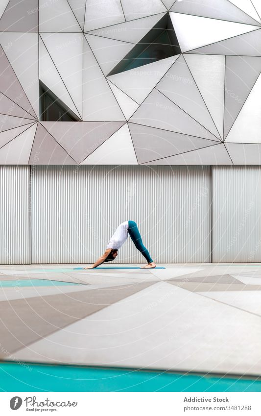 Man doing yoga in spacious room man exercise training geometry downward facing dog pose modern stretch fitness shape male sportswear architecture contemporary