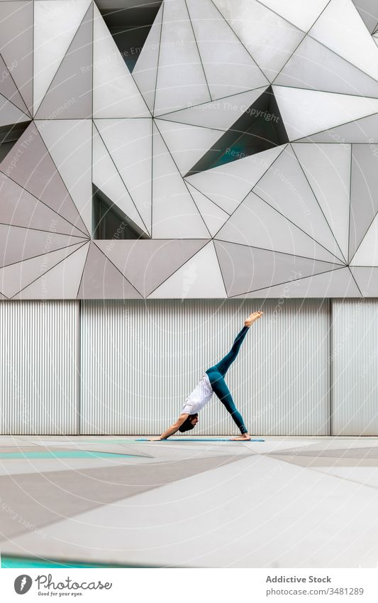 Slim guy performing yoga exercise in geometric room man training geometry modern stretch fitness shape male sportswear architecture contemporary wall spacious