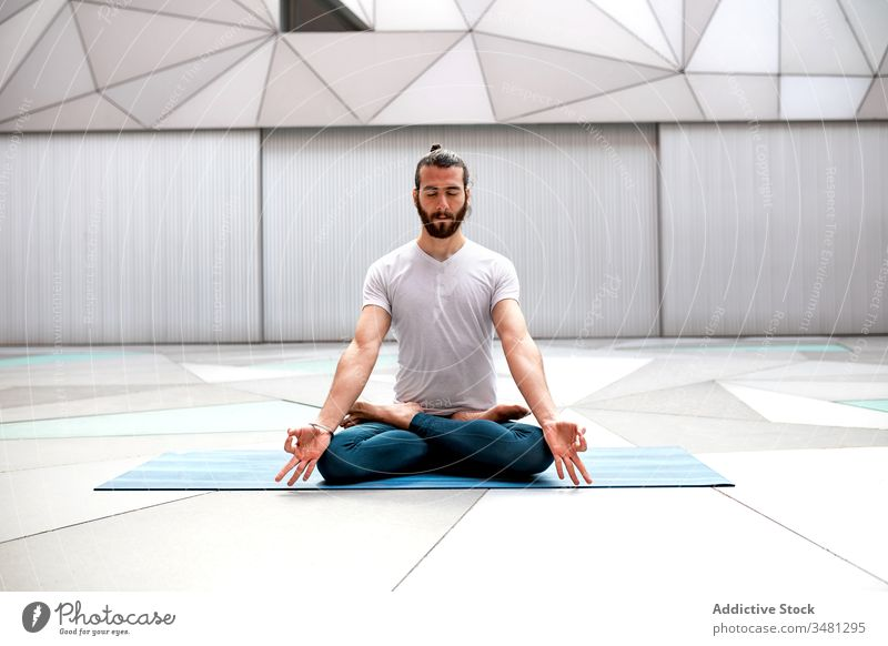 Bearded man meditating during yoga training meditate lotus pose geometry eyes closed healthy exercise relax male fitness workout legs crossed sportswear