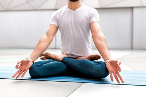 Anonymous man meditating during yoga training meditate lotus pose geometry healthy exercise relax male fitness workout legs crossed sportswear lifestyle athlete