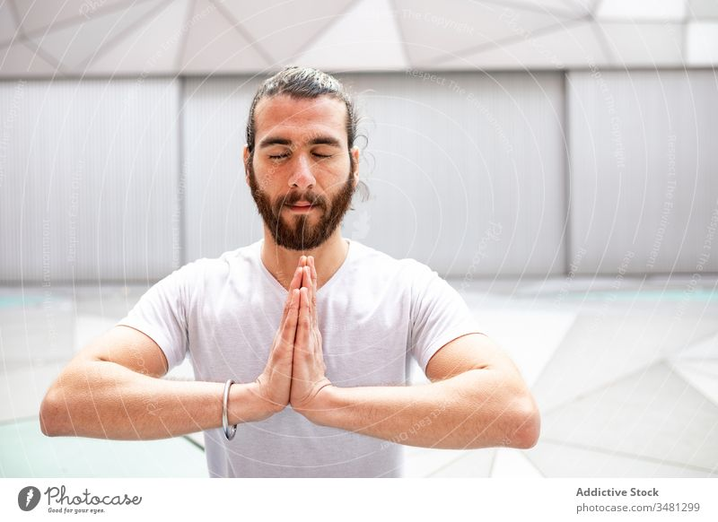 Bearded male meditating with clasped hands man meditate yoga training geometry eyes closed hands clasped healthy exercise relax fitness workout sportswear