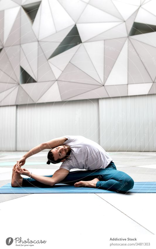 Flexible man bending to leg during yoga training exercise geometry revolved head to knee pose modern stretch fitness shape male sportswear architecture