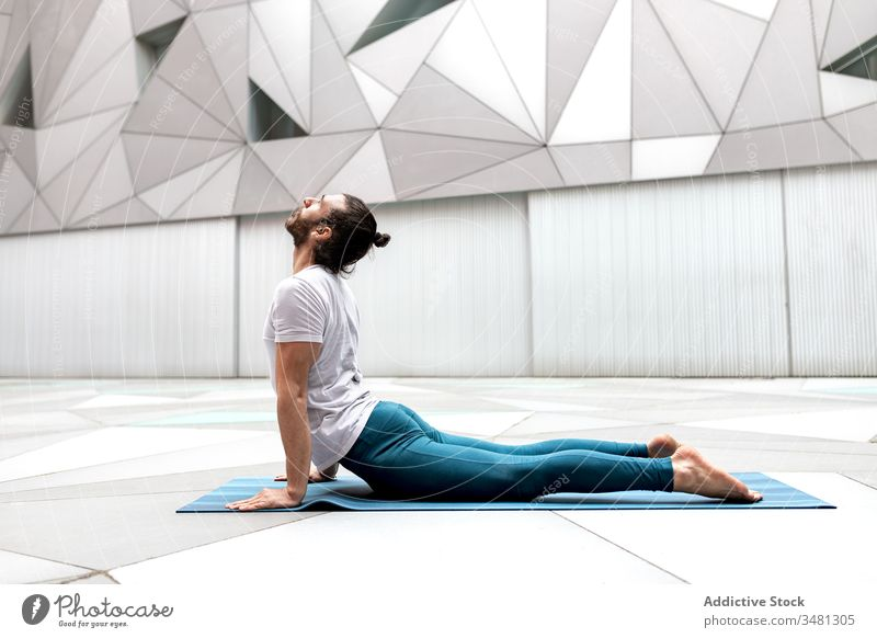 Adult man stretching back on mat yoga exercise training geometry upward facing dog pose modern fitness shape male sportswear architecture contemporary wall