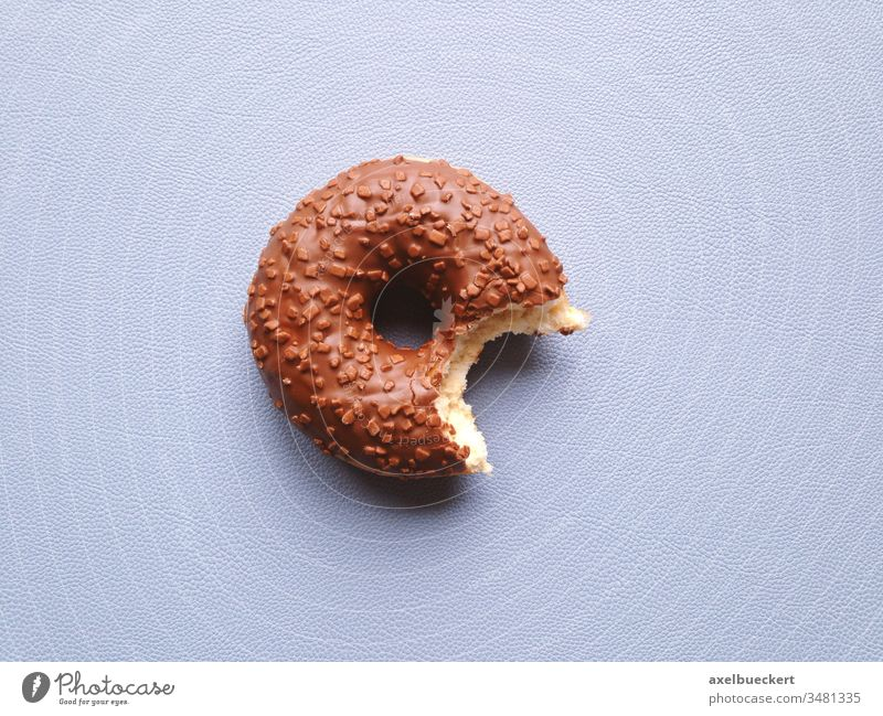 chocolate glazed donut or doughnut with bite missing half-eaten sweet food snack confectionery copy space copyspace dessert fresh indulgence unhealthy eating