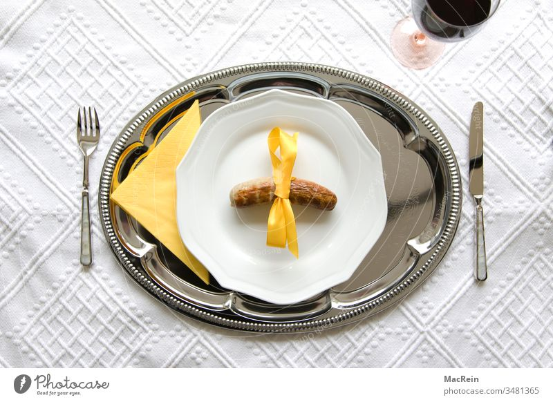 extra sausage special sausage Bratwurst Fried sausages Plate Knives Fork tablecloth Table Bow Vine Weingals Red wine Silver tray Tray Yellow nobody there