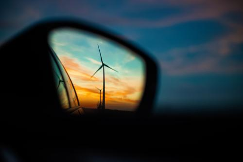 Wind turbine in the rear view mirror at sunset Wind energy plant Pinwheel Sunset Rural Side mirror Rear view mirror Mirror image Energy Energy industry