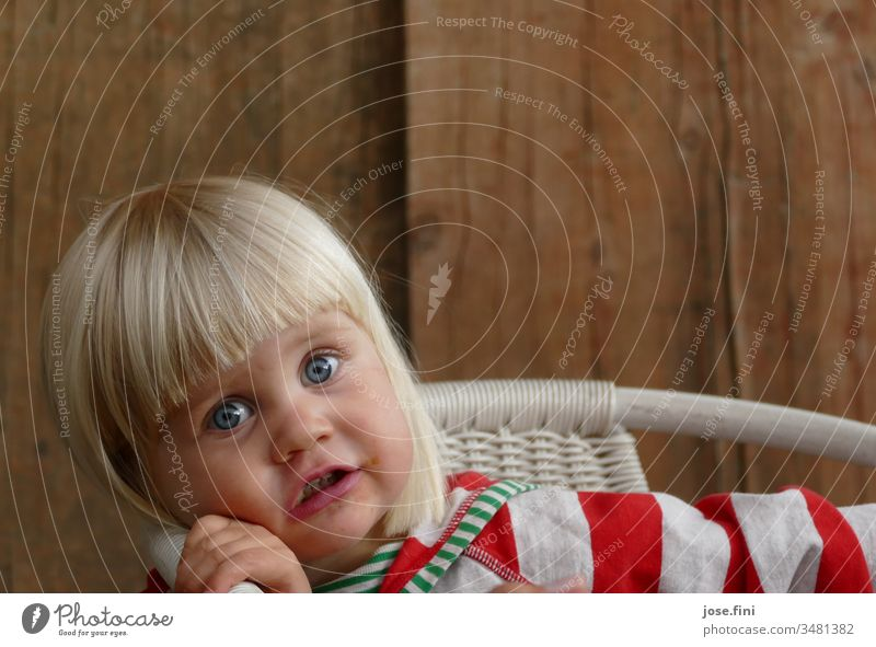 Little girl sits on a chair and looks into the camera with big eyes portrait Child little girl natural Brash Cute excited listen understand spellbound Impish