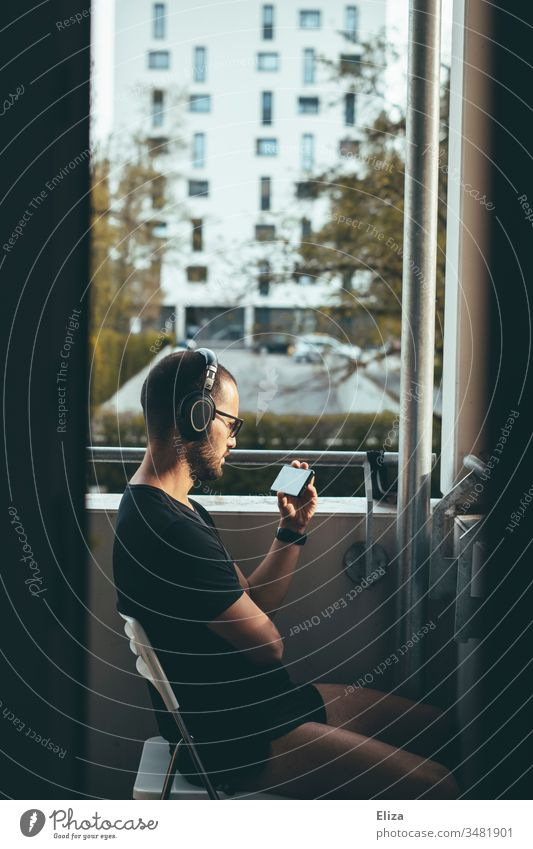 Man with headphones sits on the balcony in the evening sun and watches something on his smartphone, concept of staying home and social distancing Balcony Media