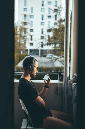 Man with headphones sits on the balcony in the evening sun and watches something on his smartphone, concept of staying home and social distancing Balcony