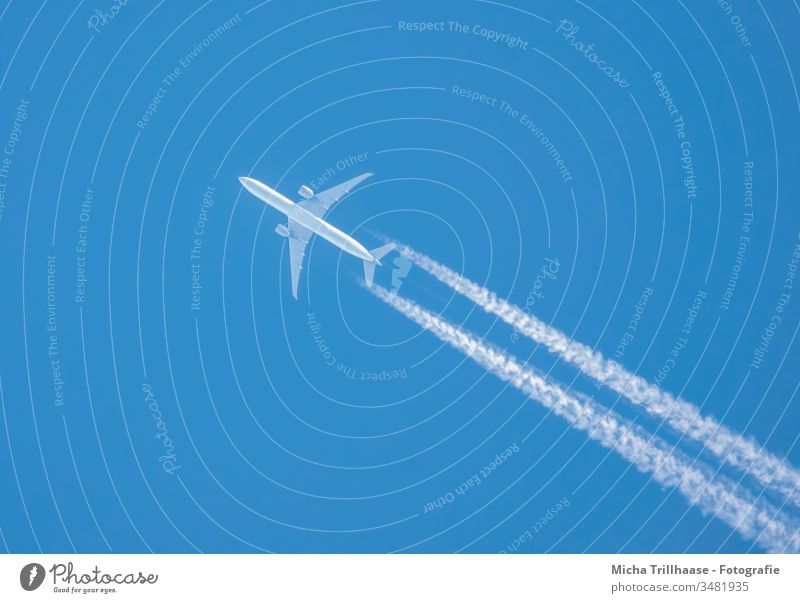 Airplane and contrails in the blue sky Vapor trail Sky Wings Engines flight travel Tourism Tourists Long distance travel Environment Climate vacation holidays