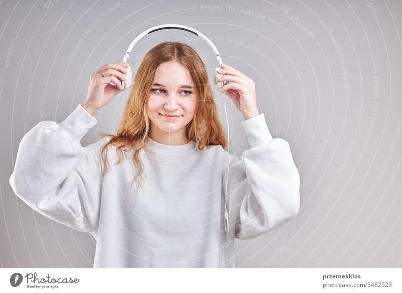 Young woman girl listening to music streaming content having fun watching video enjoying video chat talking with friends making gestures faces using smartphone earphones headphones standing over plain grey background