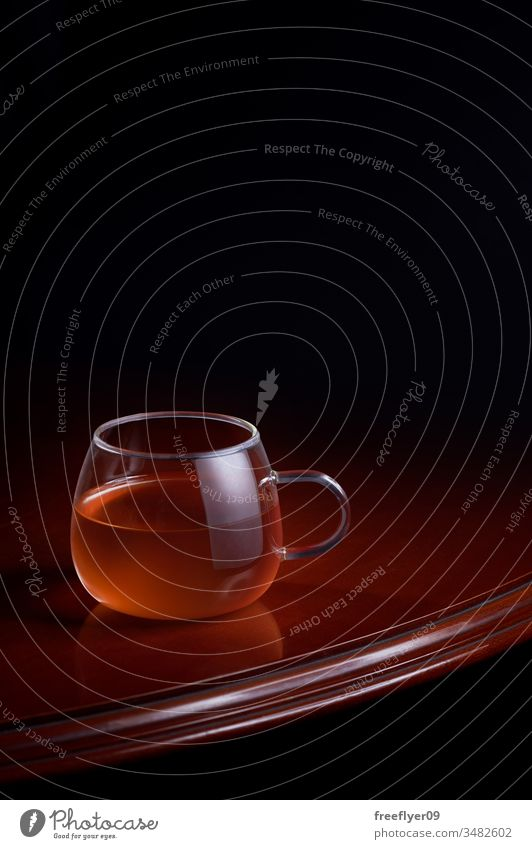 Cup of red tea on a luxurious table with a black background cup beverage hot infusion brew glass wood wooden reflection dark mint liquid antique old fashioned