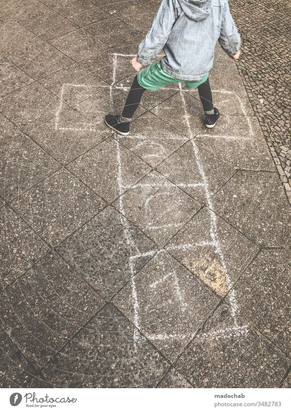 playing with the children's box - child jumps from number to number on chalk painted boxes - old children's game Hop Jump Chalk Child fun Exterior shot Playing