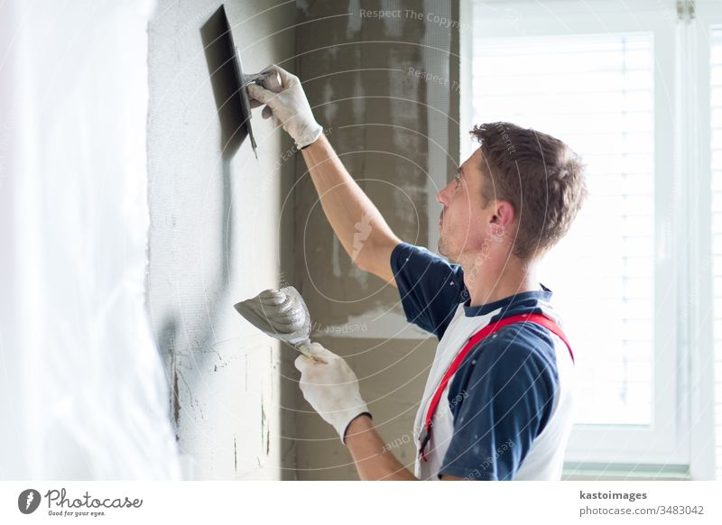 Plasterer renovating indoor walls and ceilings. construction plastering renovation worker craftsman plasterer occupation equipment repair professional building