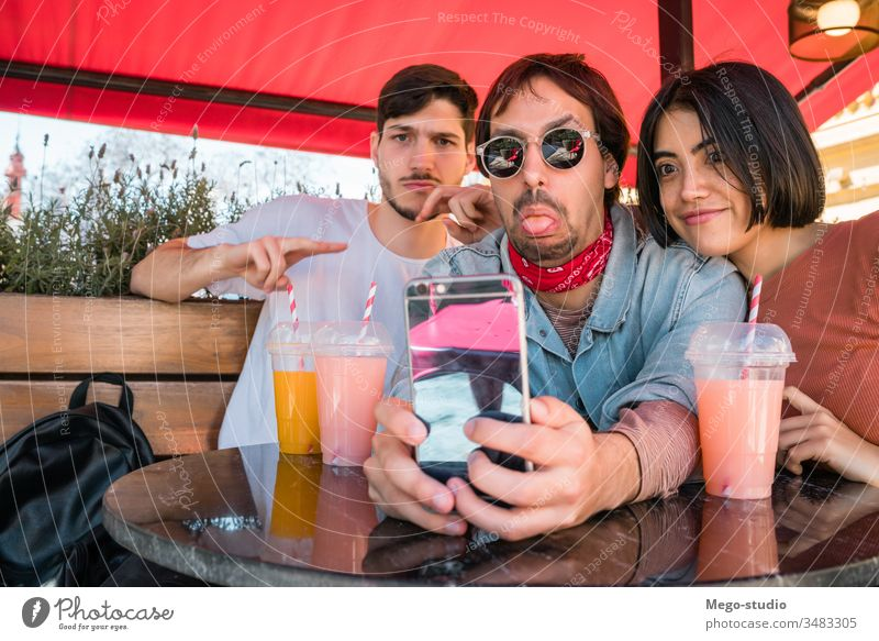 Three young friends taking a selfie with phone. happy fun together hangout four leisure looking person sitting enjoyment happiness smartphone relationship