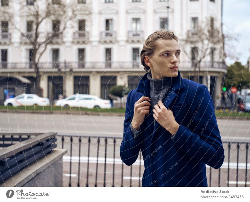 Confident young businessman in trendy outfit standing on street style elegant fashion urban coat confident serious handsome modern city wall male hairstyle