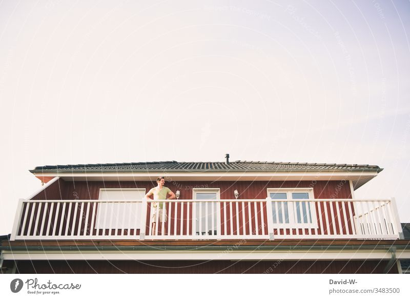 Man observes the surroundings from the balcony Observe monitored peep Curiosity see Human being Looking Adults Colour photo Exterior shot Summer Red Home